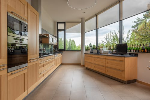 Modern cupboards with contemporary appliances placed near cabinet with kitchenware at big window overlooking green trees in stylish light kitchen