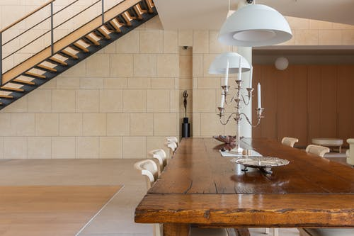 Dinner table with candlestick and chairs placed in spacious dining room with staircase and hanging lamps in modern light apartment