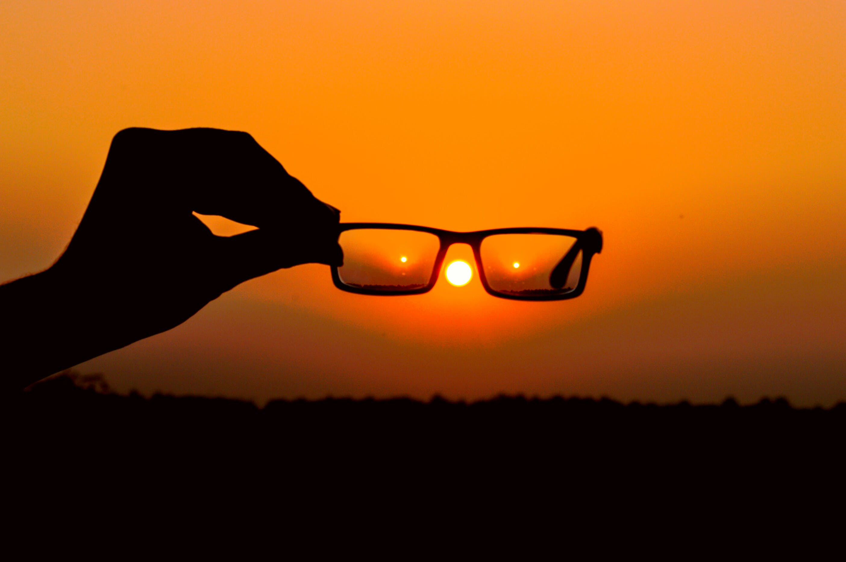 Silhouette of Person's Hand Holding Eyeglasses during Golden Hour