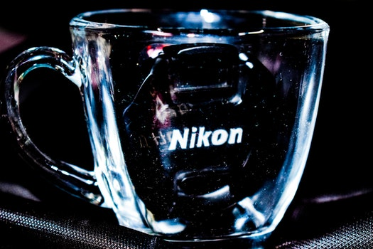 Close Up Photo Of Clear Glass Mug With Nikon Lens Cap