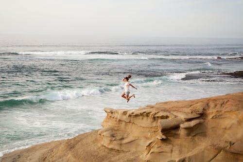 Women Wearing White Shirt Jumping on Shore