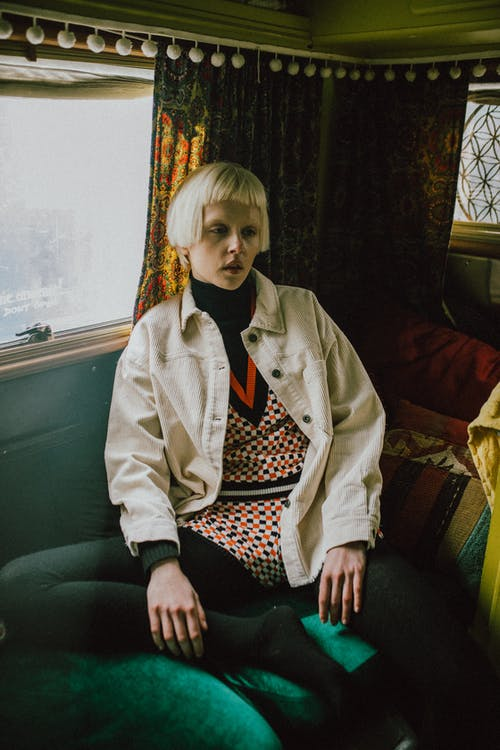 Woman in White Jacket Sitting on Green Couch
