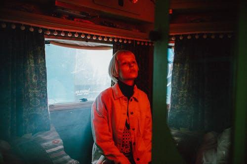 Woman in Blue Jacket Standing Near Glass Window
