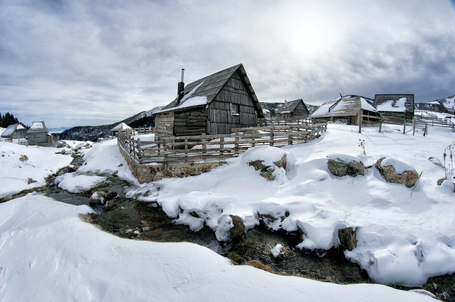 Black Wooden House Surrounded by Snow Under White Clouds