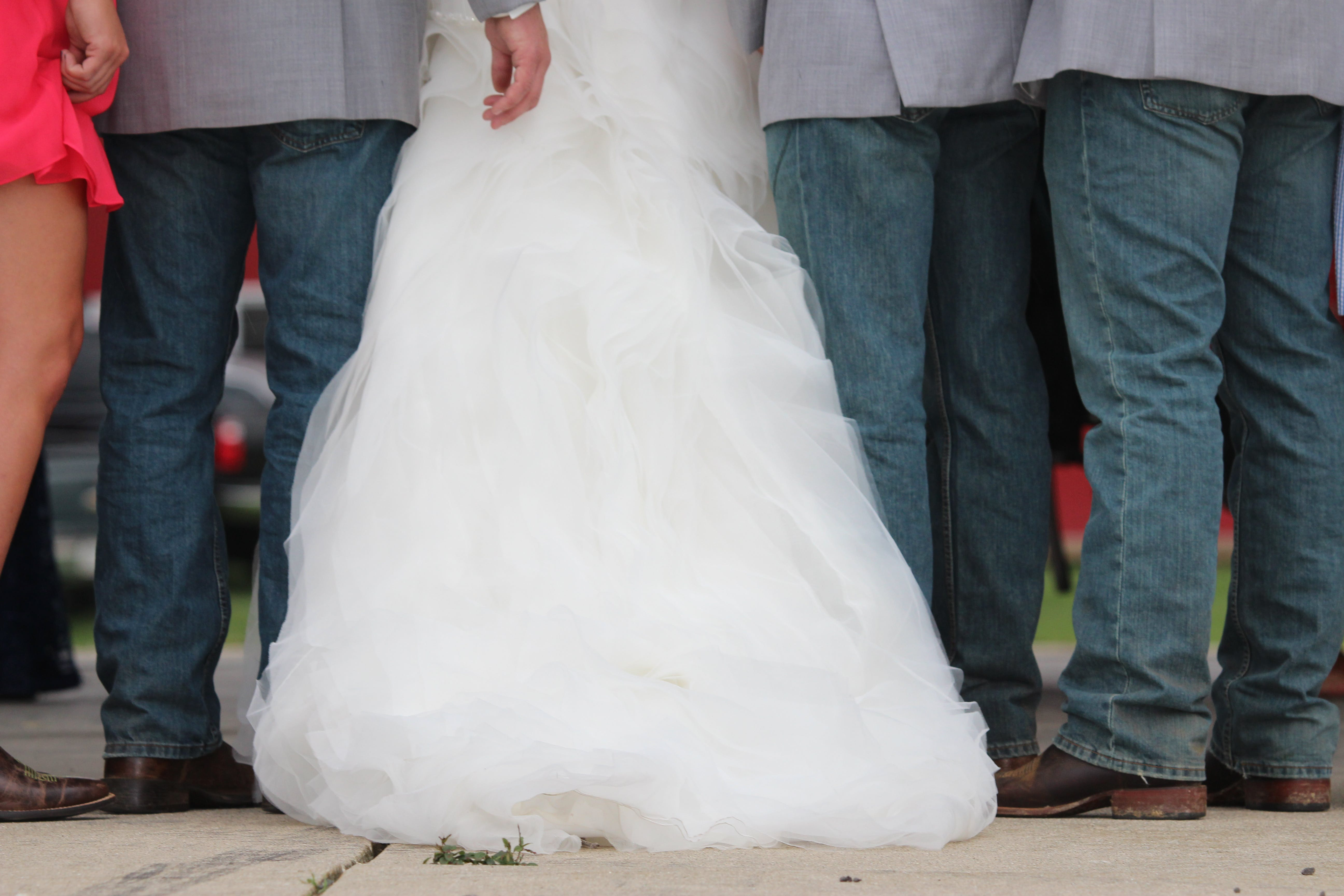 Three Men Wearing Gray Dress Shirt and Blue Denim Pants Between Woman in White Wedding Gown