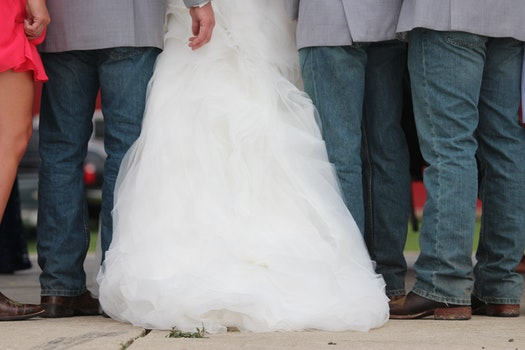 Three Men Wearing Gray Dress Shirt and Blue Denim Pants Between Woman in White Wedding Gown