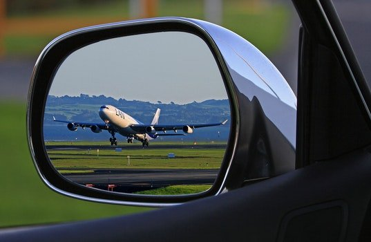 White Airplane Reflection on Car Side Mirror