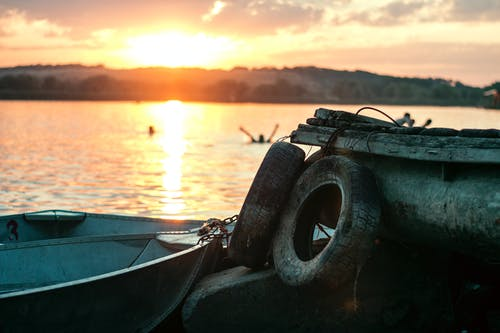 White Boat on Dock Near Two Auto Tires during Sunset