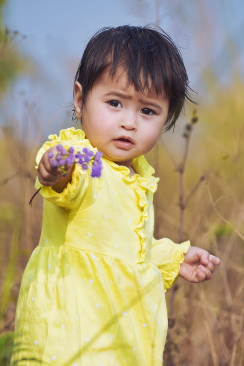 Close-Up Shot of a Girl in Yellow Dress Holding a Purple Flower