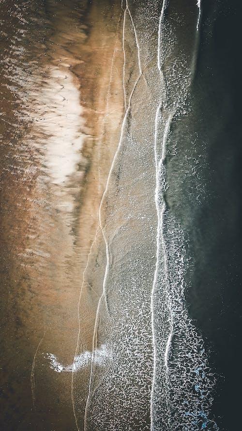 Aerial top view of clear blue water of ocean rolling on sandy coastline