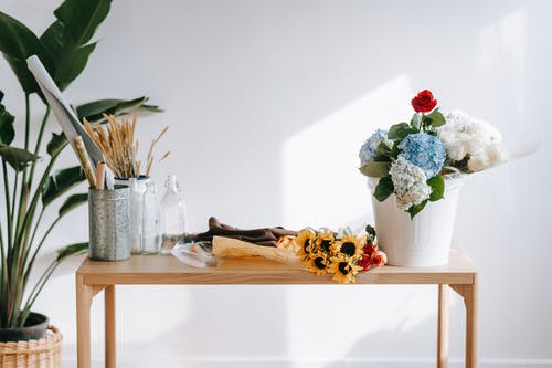 Bouquet of hydrangeas and rose on table with sunflowers