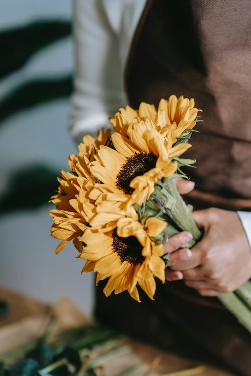 Florist with bunch of fresh sunflowers