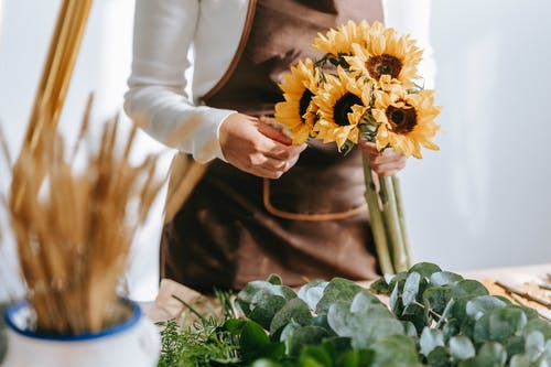 Crop anonymous female seller in floral shop with bunch of blooming sunflowers standing near table with green plants