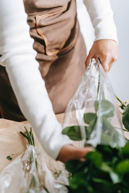 Woman wrapping flowers in plastic package