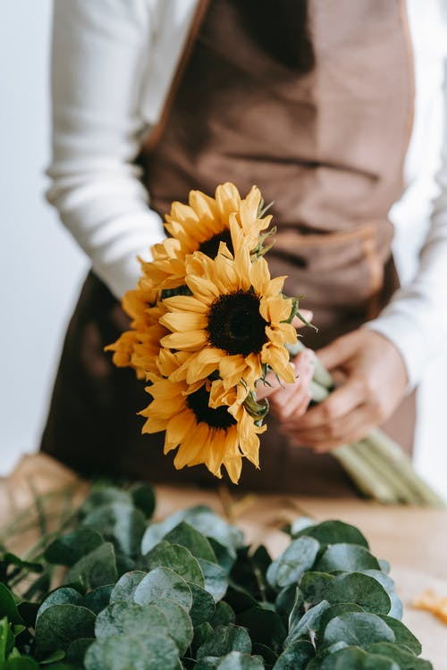 Crop anonymous female florist in apron standing at table with blooming sunflowers in floral store