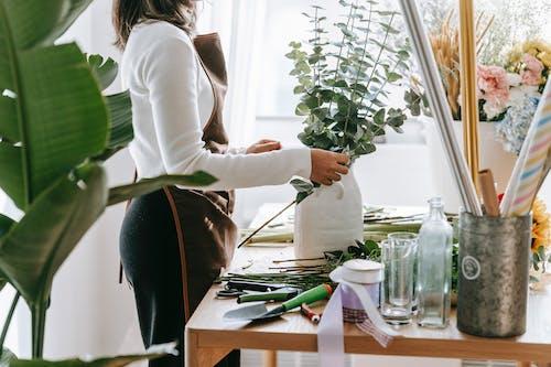 Crop florist against Eucalyptus and blooming flowers at work