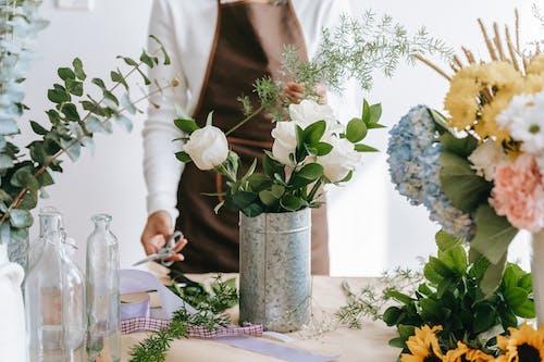 Crop florist with scissors composing flower bouquet in workspace