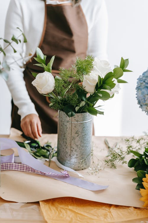 Crop anonymous woman in brown apron arranging festive bouquet of gentle white roses in metal bucket