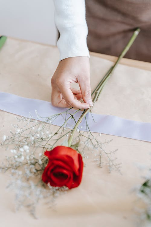 Florist preparing red rose with white flowers on ribbon