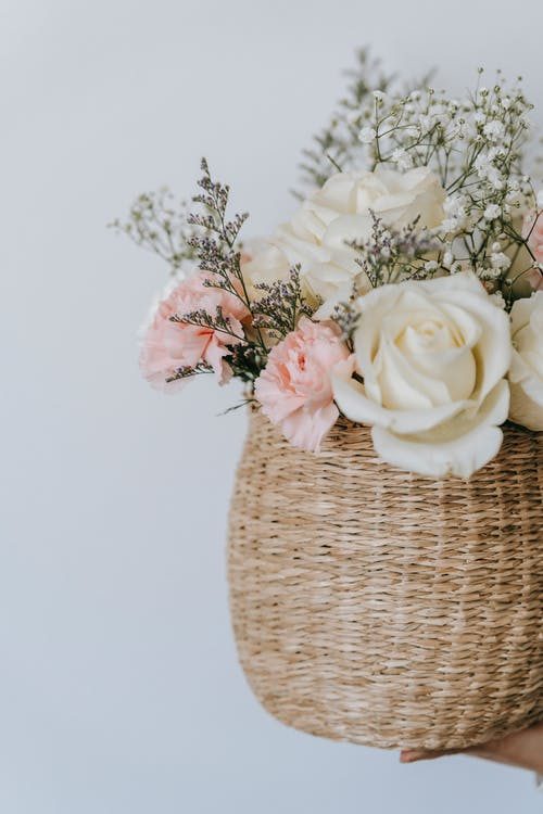 Wicker basket with flower bouquet on white background