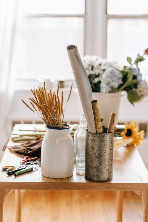 Wooden table with flowers and tools in light room