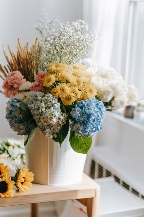 Lush composition of multicolored flowers in vase on wooden table against blurred background