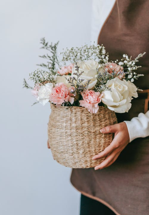 Crop anonymous female in apron standing with wicker basket with bunch of delicate roses in floral shop