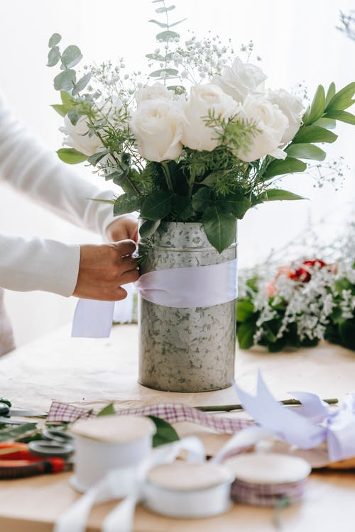 Crop anonymous female florist tying bow on bunch of fresh white roses with decorative branches in floral shop