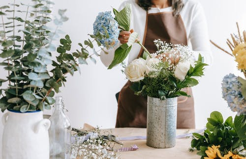 Crop unrecognizable female florist arranging hydrangea flowers into vase with roses while standing at table with assorted plants in room