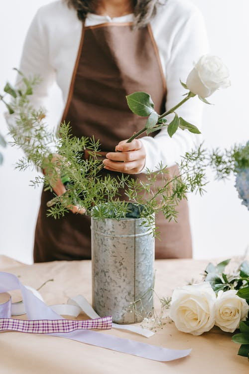 Anonymous woman putting flower into vase