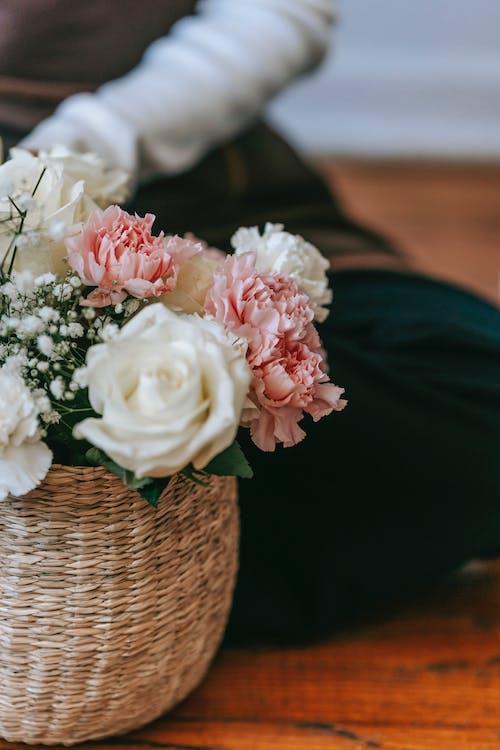 Unrecognizable person near flowerpot with various flowers