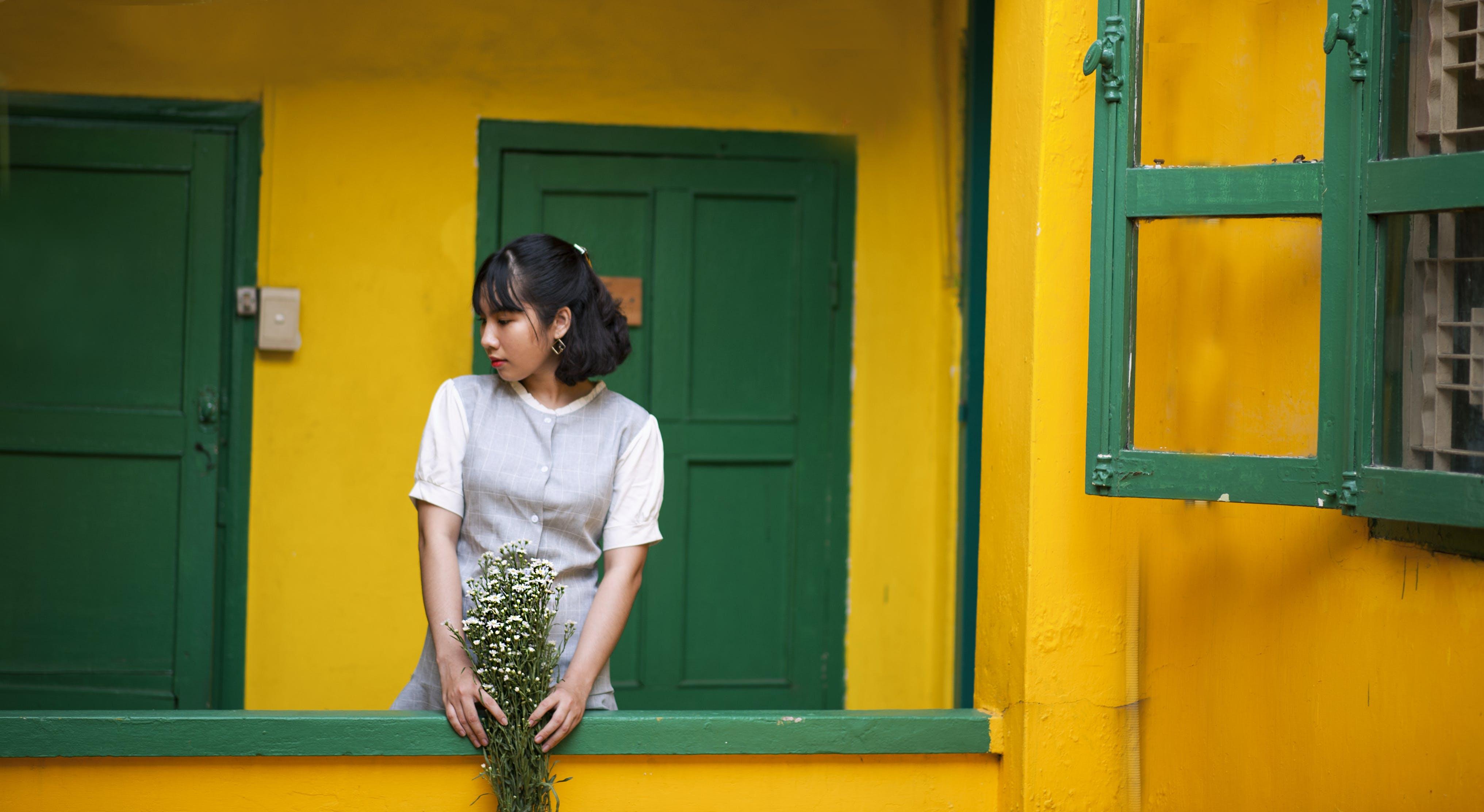 Woman Holding Flower Standing Behind Door