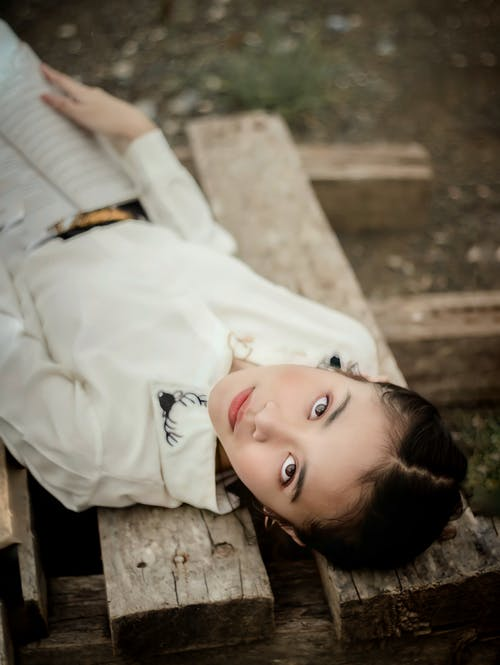 Woman in White Dress Lying on Wooden Floor