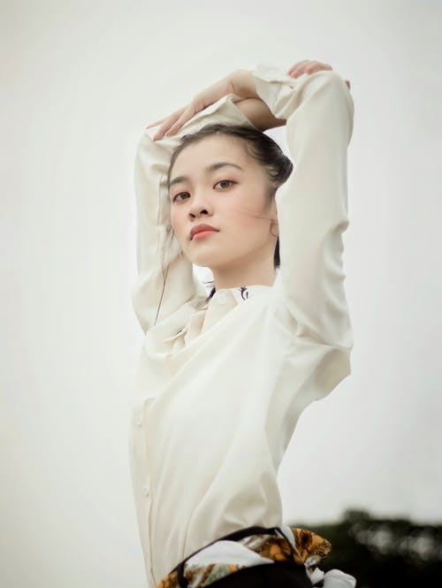 Confident Asian female with raised arms under gray sky