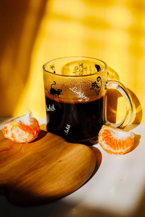 Glass of hot aromatic coffee with halved tangerine near chopping board in sunlight