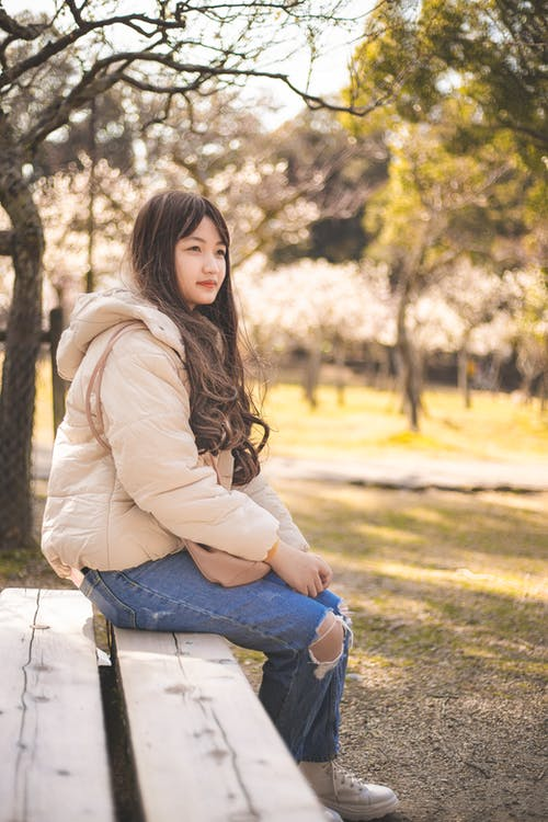Woman in Beige Jacket and Blue Denim Jeans Sitting on Brown Wooden Bench