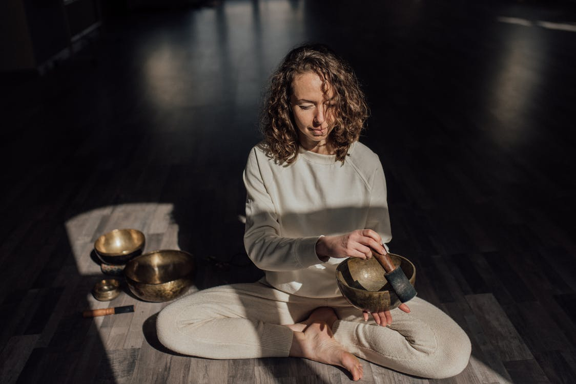 Female sound therapist sitting with crossed legs on parquet while playing singing bowl with mallet during meditation practice