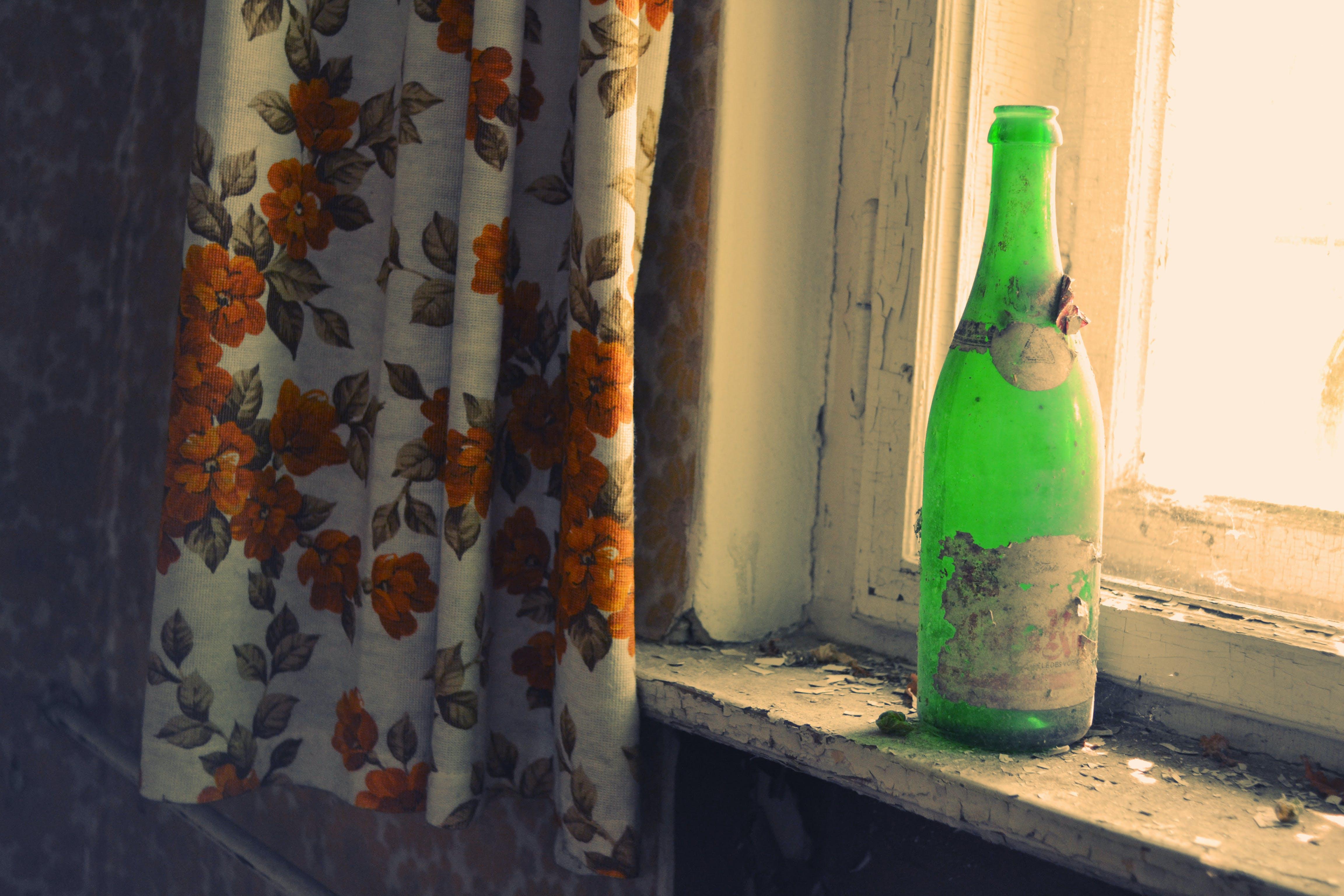 Green Glass Bottle Beside Window