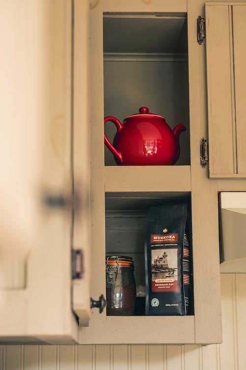 Red Ceramic Teapot on Brown Wooden Shelf
