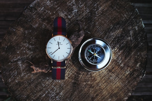 Round Silver-colored Analog Watch Beside Compass