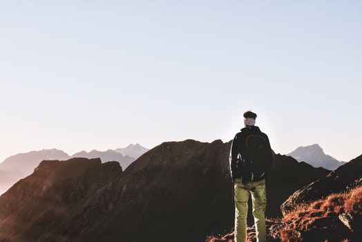 Person Standing on Top of the Mountain
