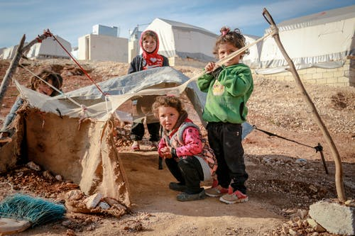 Cute ethnic poor children playing in shabby yard