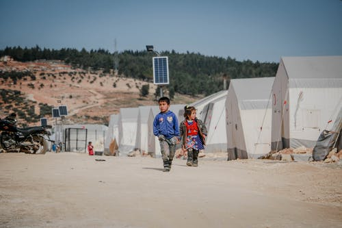 Ethnic boy and girl in shabby clothes walking on dusty road near tents on sunny day in refugee camp