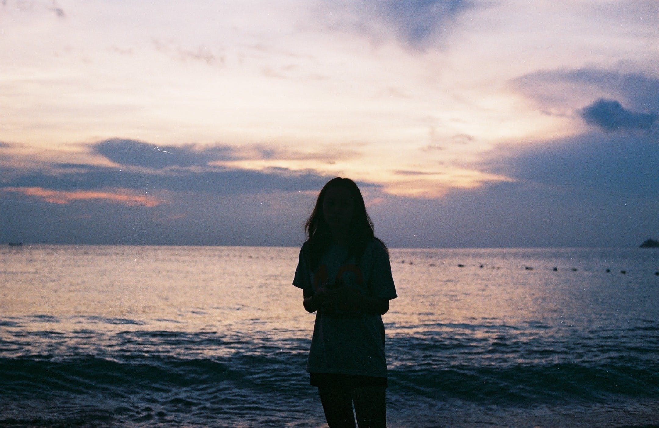 Silhouette of Woman Standing Near Large Body of Water