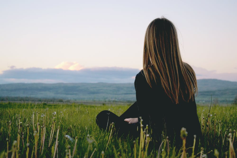 A teenage girl sitting on the green grass field. | Photo: Pexels