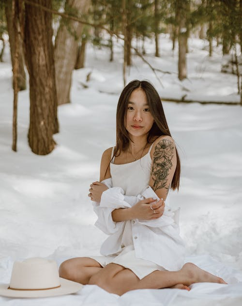Full body of alluring young barefooted Asian female model with long dark hair in light white dress sitting on snowy ground near coniferous trees and looking at camera