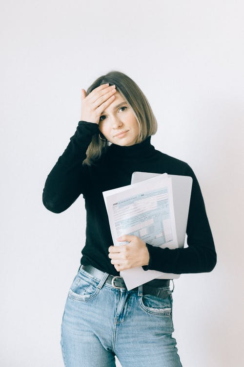 Woman in Black Turtleneck Shirt Holding Tax Forms