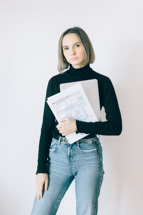 Woman in Black Long Sleeve Shirt Holding Tax Forms