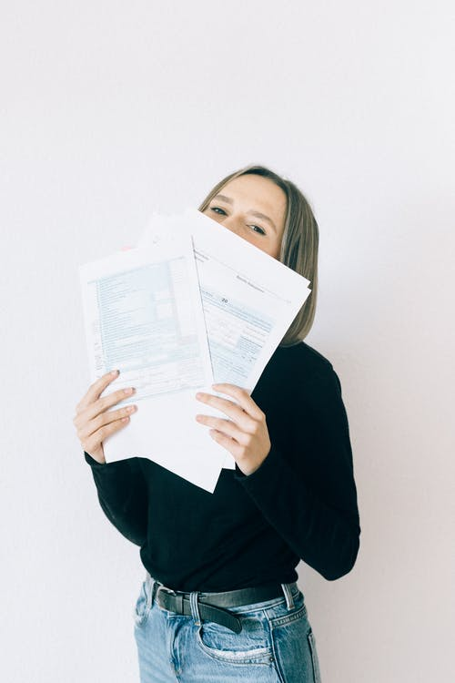 Woman In Black Shirt With Gray Hair Holding Tax Forms
