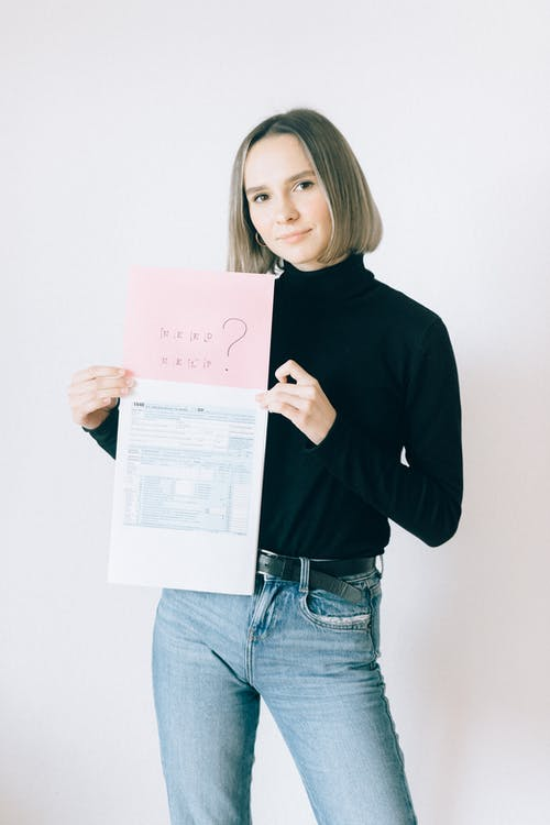 Woman in Black Long Sleeve Turtleneck Shirt Holding Tax Forms and Offering Help
